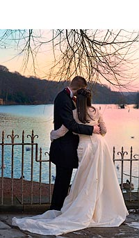 Romantic: bride and groom looking out across water at beautiful sunset.