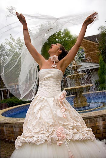 Bride in front of a fountain holding her veil in the air.
