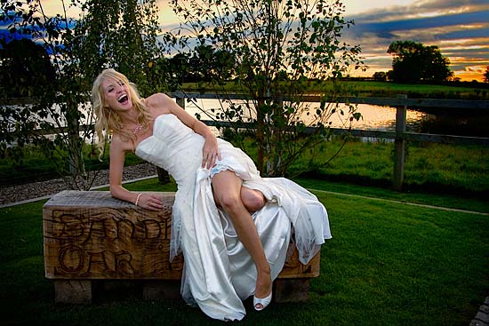 Bride sitting on wooden seat with sunset backdrop at Sandhole Farm, Cheshire.
