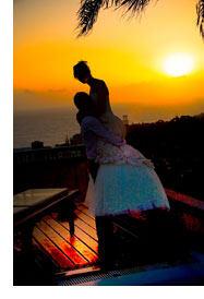 Romantic sunset wedding - Groom is lifting up bride.